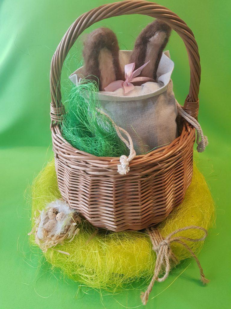 Cestino con sacchetto di lino, dal quale spuntano le orecchie di un coniglietto di feltro di lana pettinata.