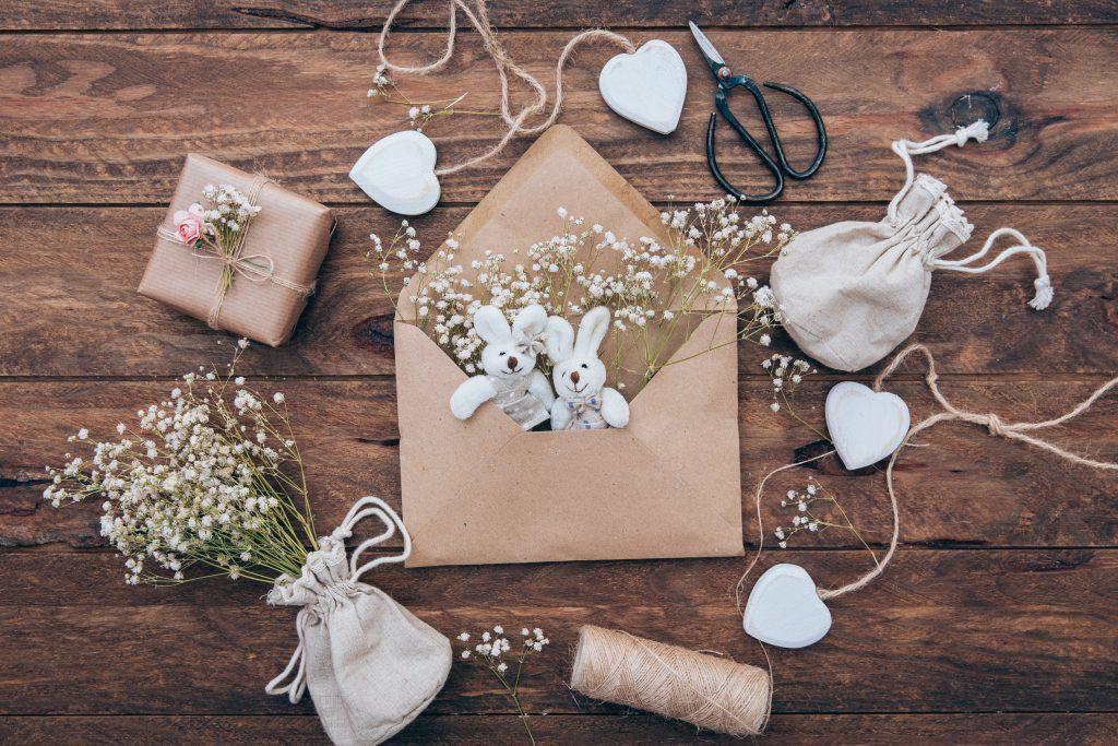 Borsa in lino con intonaco, morbidi coniglietti in una busta e un regalo avvolto in carta grigia