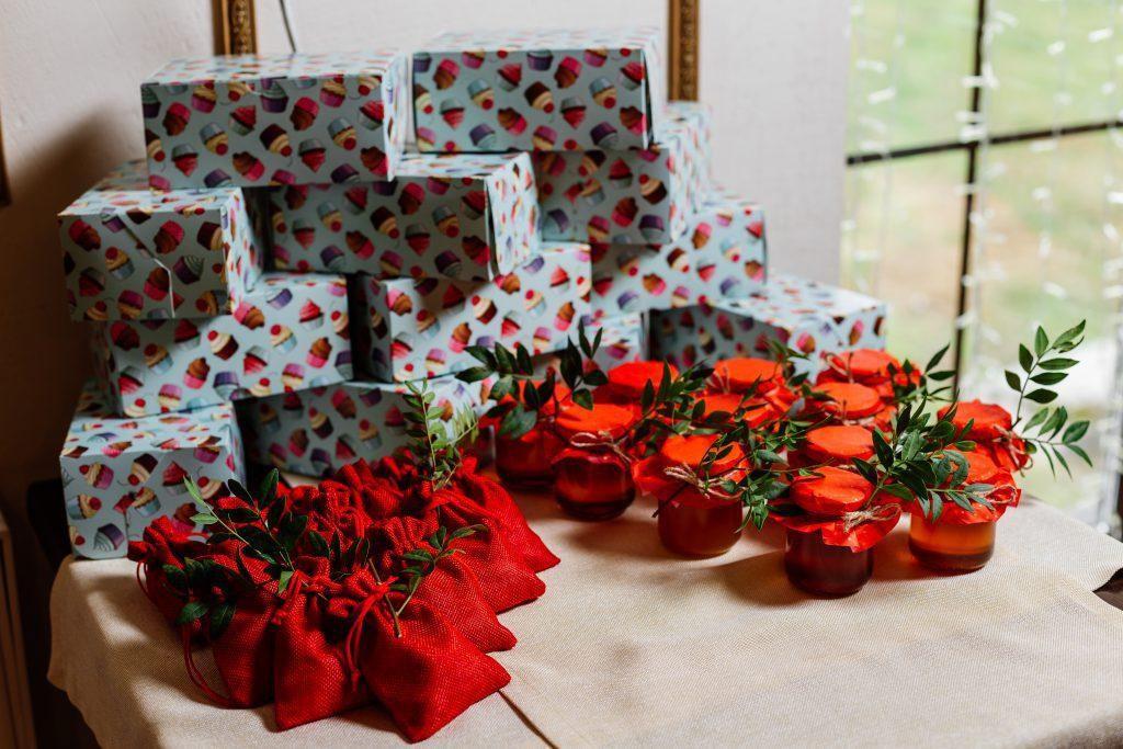 Scatole regalo avvolte in carta colorata, sacchetti di iuta rossa e vasetti con conserve
