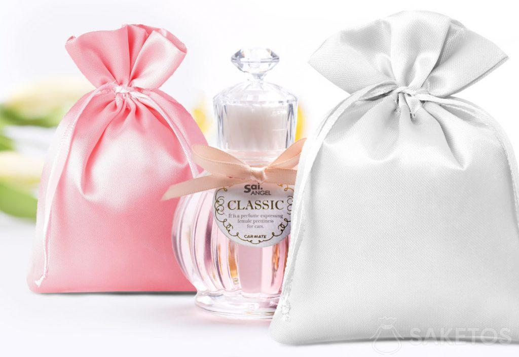 Sacchetti di raso di colore rosa e argento e bottiglia decorativa di profumo