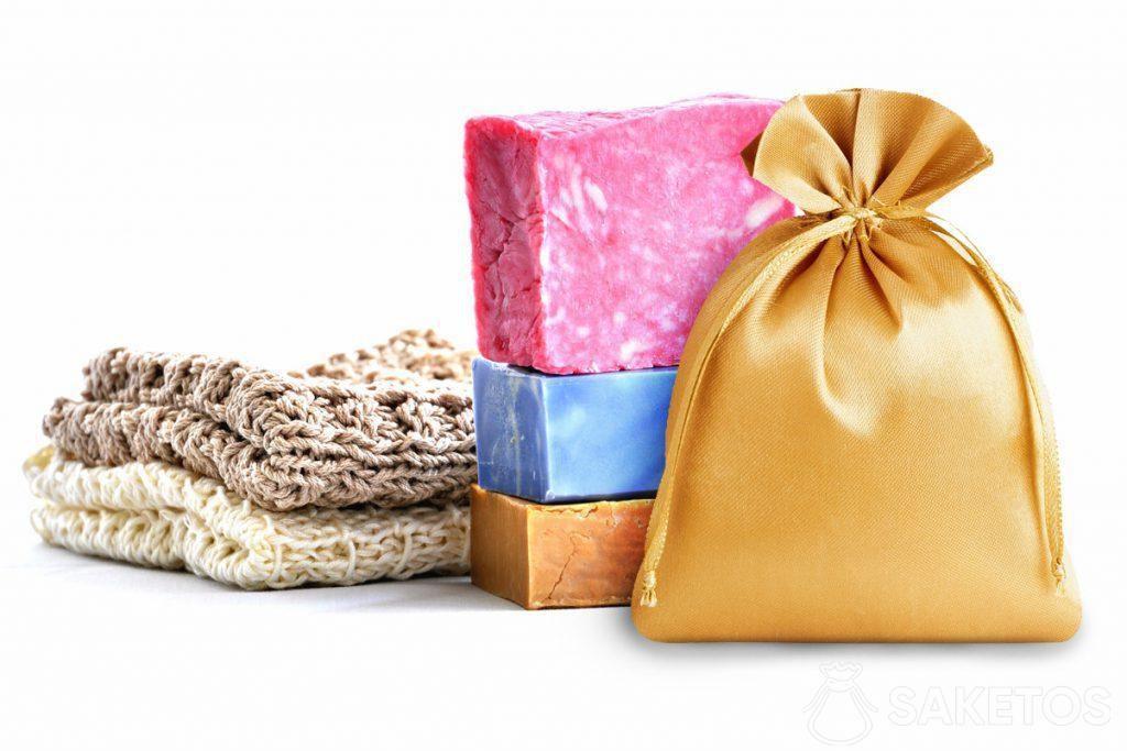 Sacchetto dorato di raso su uno sfondo di saponette colorate.