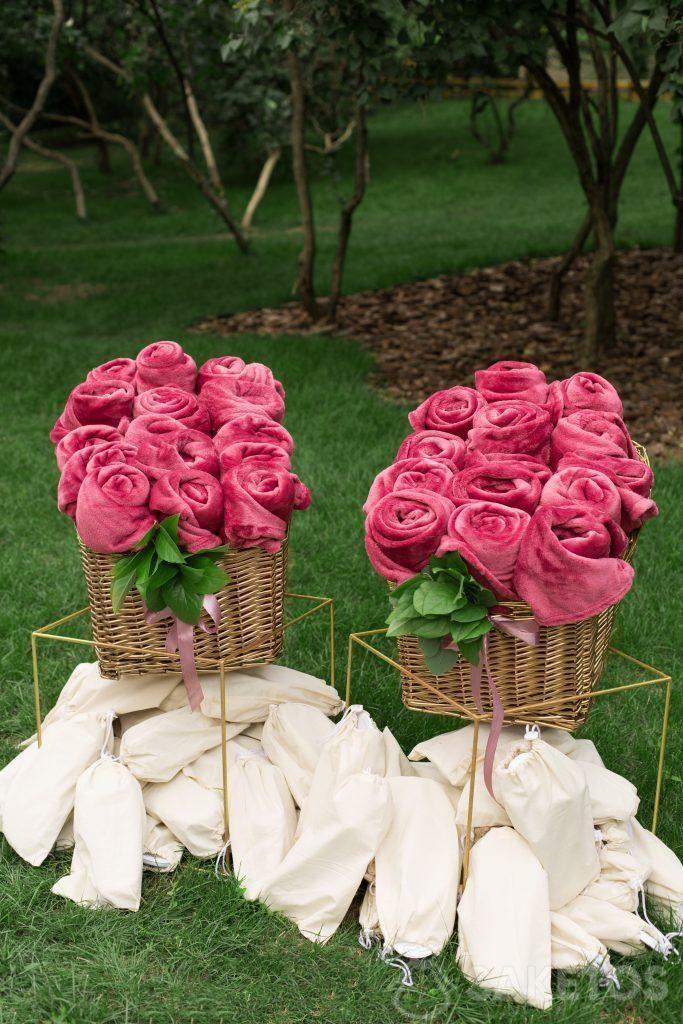 Coperte arrotolate decorate e pantofole in sacchetti di lino preparati per gli ospiti del matrimonio