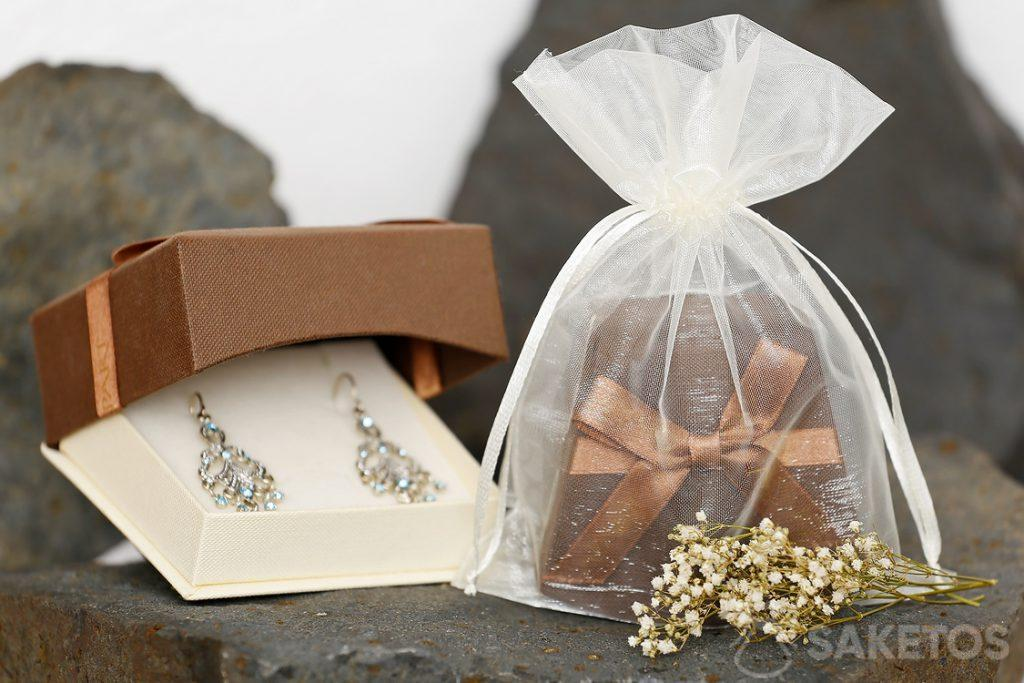 Una scatola regalo con gioielli confezionata in un sacchetto di organza ha un aspetto particolarmente elegante.