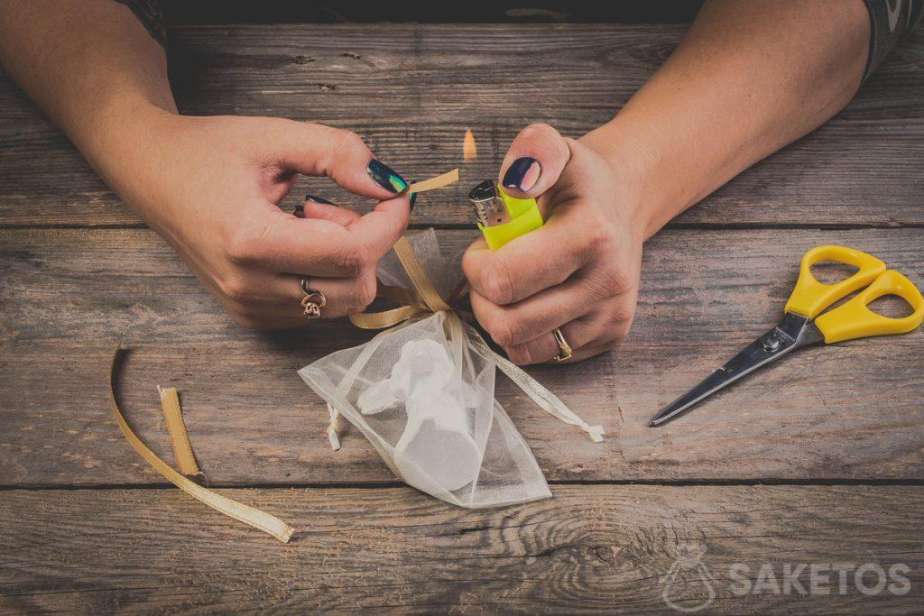 Ricordati di bruciare le estremità del fiocco. Questo eviterà che il nastrino si sfilacci - passo 12