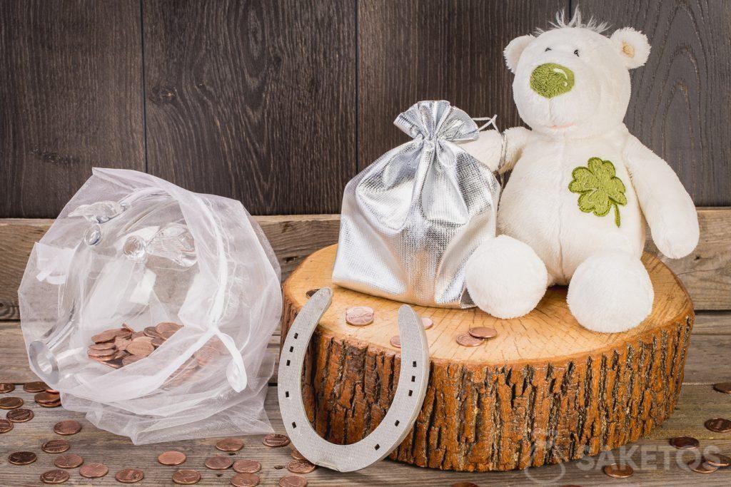 I soldi in regalo possono essere messi in un sacchetto di tessuto appeso alla zampa di un orsetto di peluche. Un'altra ottima idea è regalare un porcellino salvadanaio pieno di monete