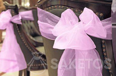 Dekorativní mašle z organzy zavázaná na zadní straně židle