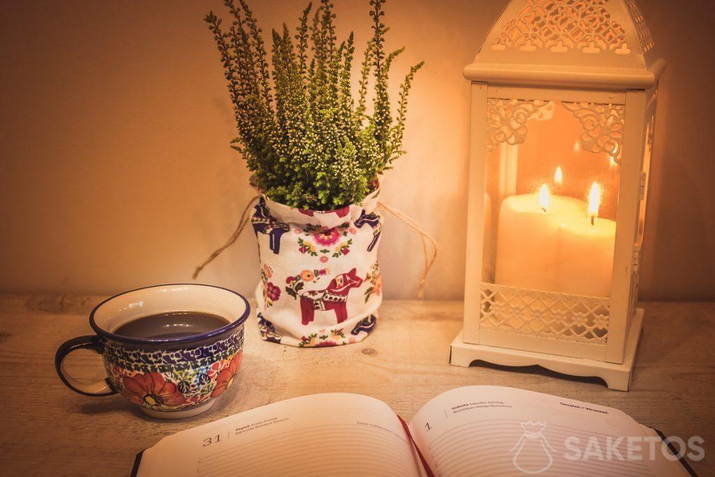 Stół ozodbiony lampionem i kwiatem w osłonce z materiałowego woreczka