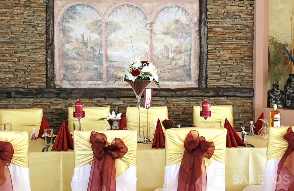 Kokardy z organzy na krzesłach oraz wazon i świeczniki na weselnym stole