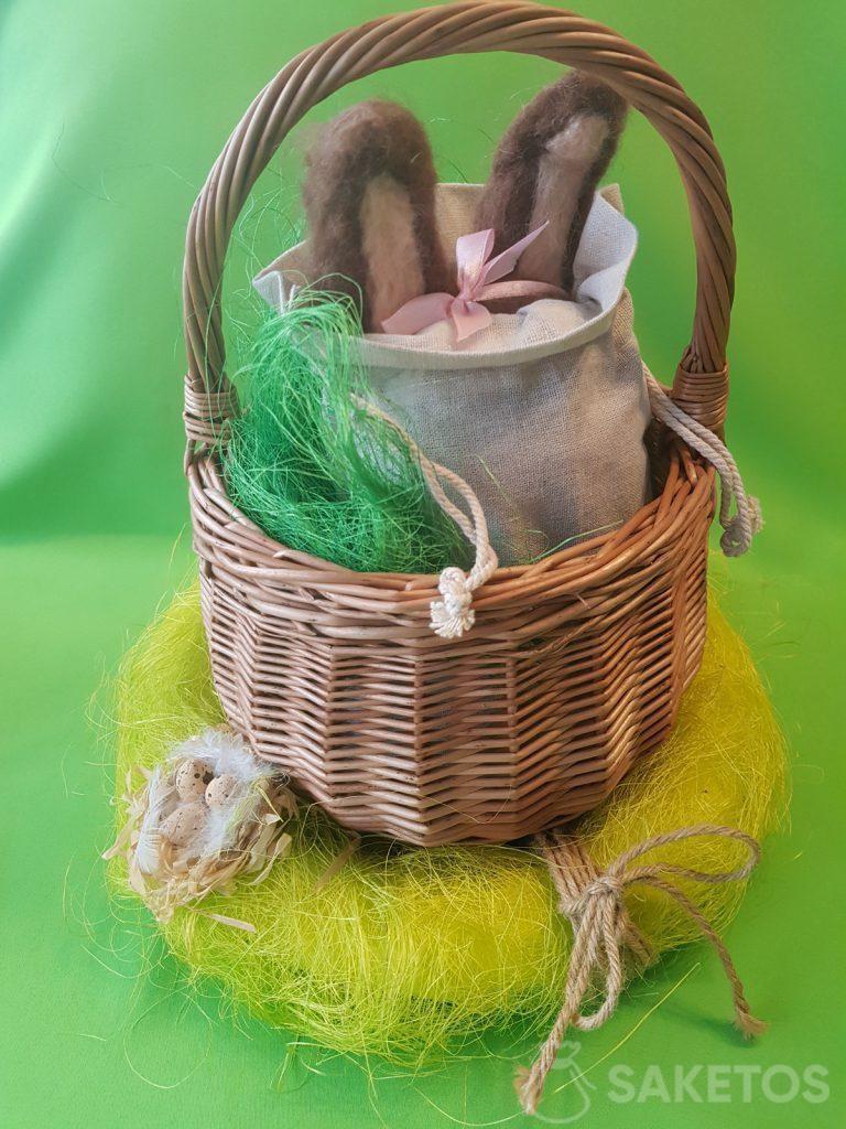 Un cestino con un sacchetto di lino, da cui sporgono le orecchie di feltro di lana di coniglio.