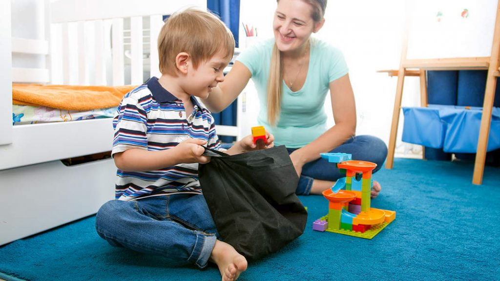 1.Un bambino prende dei mattoncini da una borsa in tessuto